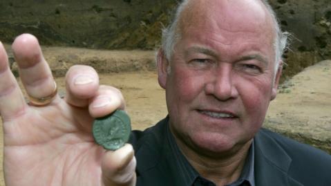 L'archeologo britannico Tony Clunn mostra una delle monete romane trovate nel luogo della battaglia della Selva di Teutoburgo