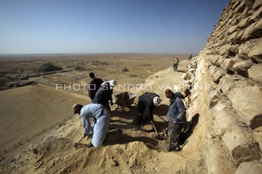 Operai al lavoro sul fianco della piramide che domina la piana di Saqqara