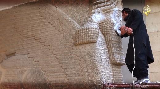 A colpi di martello contro un lamassu (toro alato androcefalo) da Nimrud al museo di Mosul