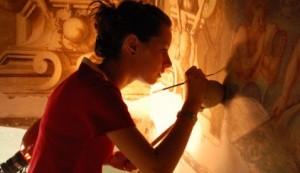 Una giovane restauratrice al lavoro su un affresco