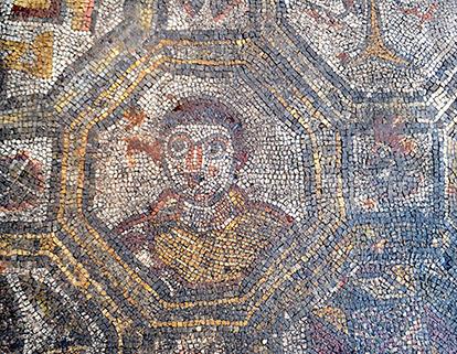 Il busto umano raffigurato all'interno di una cornice ottagona sul pavimento musivo della villa dell'Oratorio