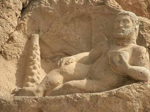 La statua colossale di Ercole nudo scolpita sulla roccia nel sito archeologico di Bisotun (Iran occidentale)