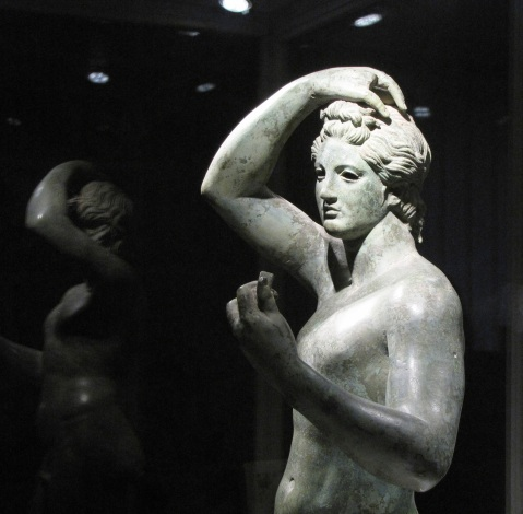 L'Efebo di Sutri: figura maschile giovanile, con il braccio destro sul capo e il sinistro piegato in modo da portare ad altezza del volto un oggetto ora mancante, forse uno specchio