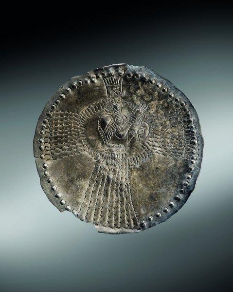 Placchetta circolare in argento del periodo neo-assiro con la rappresentazione del dio Assur